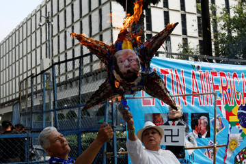 Activist burn a pinata with the picture of U.S. President Donald Trump during the international labor Day demonstration in Mexico City