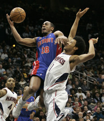 Detroit Pistons guard Arron Afflao goes for a layup over Atlanta Hawks guard Josh Childress in the first half of their NBA basketball game in Atlanta