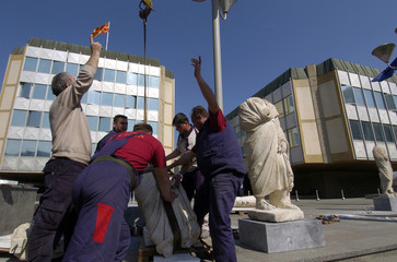 Workers install an ancient statue in front of the Macedonian government building in Skopje
