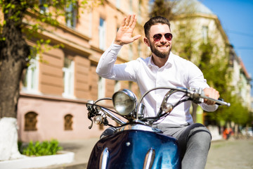 Cheerful young bearded man in helmet is sitting on scooter and say hello on city street