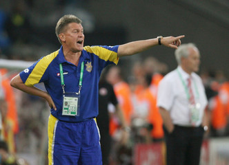 Ukraine coach Oleg Blokhin shouts instructions as Switzerland coach Koebi Kuhn watches play during second round World Cup 2006 soccer match in Cologne