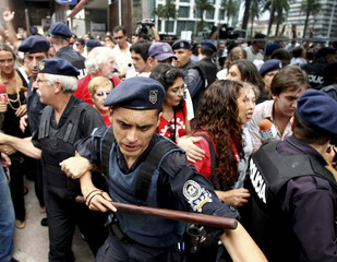 Police officers protect members of an Argentine environmentalist group as they are insulted by people in Montevideo