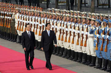 Japanese Prime Minister Abe and Chinese Premier Wen review the honour guard during a welcome ceremony in Beijing