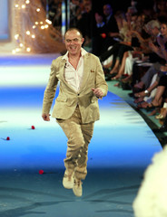French designer Christian Lacroix runs onto the catwalk at the end of his Haute Couture 2003-2004 Au..