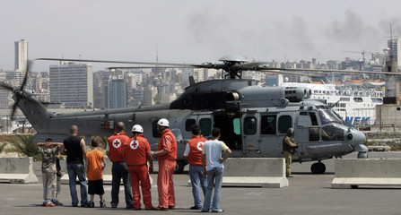 Lebanese civilians and members of Red Cross wait for French helicopter to land on Beirut port