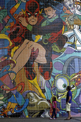 A man and a girl look at a wall decorated with with comics characters on a street in Lisbon