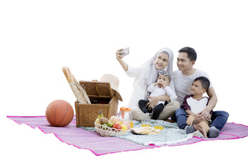 Family taking selfie photo while picnic