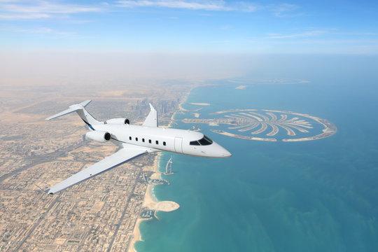 Business jet airplane flying over Dubai city and sea coastline.