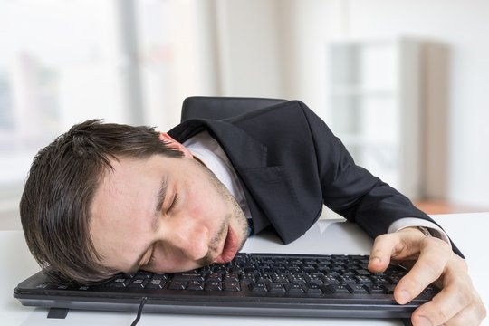 Exhausted or tired businessman is sleeping on keyboard in office.