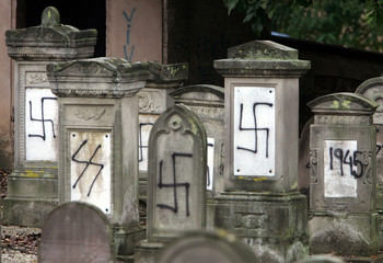 Graves desecrated by vandals with Nazi swastikas and anti-semitic slogans in the Jewish cemetery of ..
