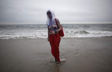 A participant walks on the beach during the Mermaid Parade in Coney Island in New York