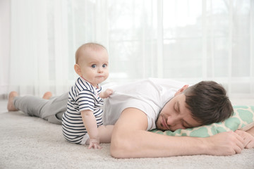 Father fall asleep with cute baby daughter on carpet at home