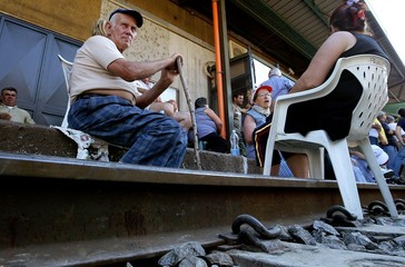 ELDERLY PEOPLE ARE SEATED IN THE MIDDLE OF THE RAIL DURING A PROTEST IN SOUTHERN ITALY.