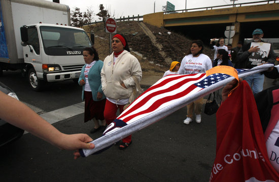 Legal US residents waiting for citizenship march to the Dallas US Citizenship and Immigration Services office to protest delays in the processing of their applications
