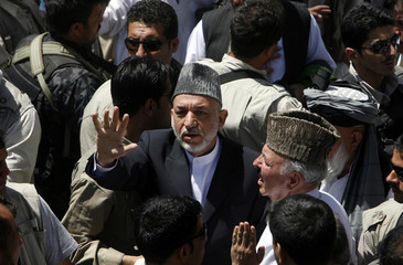 Afghanistan's President Karzai waves at his supporters during a campaign gathering in Kaihan valley of Baghlan province