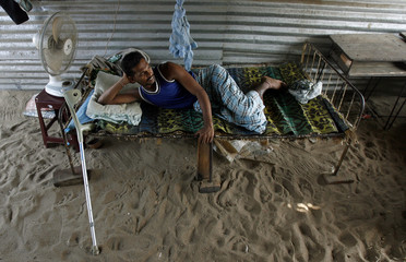 A man rests inside a temporary shelter at the Kaliyakadu camp for internally displaced Tamil people in Batticaloa