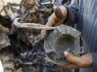 A man holds a part of a bomb found at the scene of twin bomb attacks in Baghdad