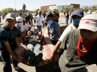 People carry an injured protester after clashes with Federal police officers outside the University Benito Juarez in Oaxaca City