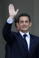 France's President Nicolas Sarkozy waves at Elysee Palace in Paris