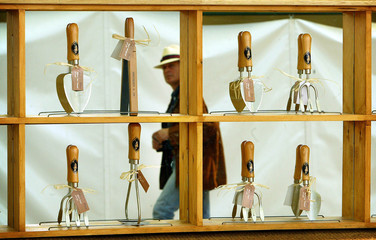 MAN WALKS PAST GARDEN TOOLS FOR SALE AT THE CHELSEA FLOWER SHOW IN LONDON.