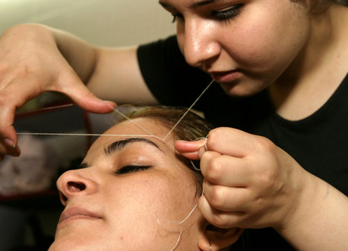 An Iraqi bride undergoes a hair removal technique called 'threading' at a beauty parlor in Baghdad M..