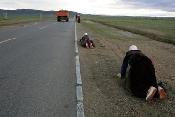 Tibetan pilgrims crawl while they worship along a highway near Namtso Lake in Tibet Autonomous Region