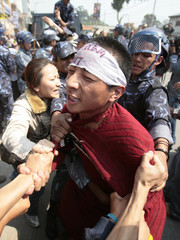 A Tibetan protester struggles with police officers in front of the United Nations building in Kathmandu