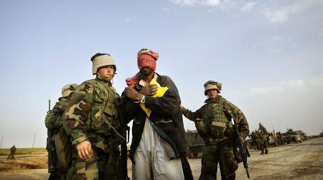 U.S. MARINES GUARD DETAINED IRAQI MAN NEAR SHOOTING SCENE IN CENTRALIRAQ.