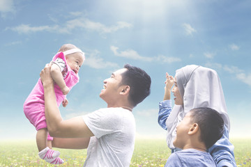 Muslim family playing with baby on meadow