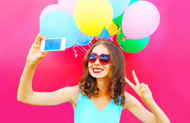 smiling woman in a birthday cap is taking a picture on a smartphone with an air colorful balloons on a pink background