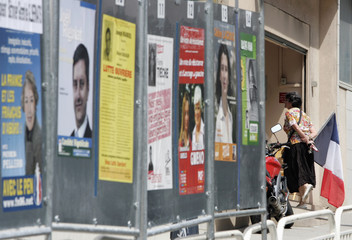 A French citizen enters a polling booth during the first round of the French parliamentary elections in Nice