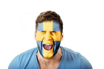 Screaming man with Sweden flag on face.