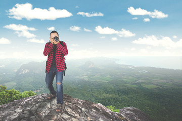 Young man taking photo on mountain