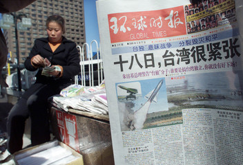 CHINESE VENDOR SELLS NEWSPAPERS ABOUT TAIWAN ELECTIONS IN BEIJING.