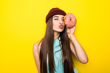 beautiful excited hipster girl in red hat holding pink donut with kiss near yellow wall