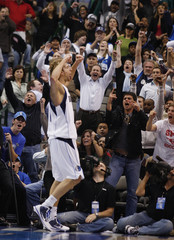 Fans celebrate along with Mavericks Nowitzki after he hit a shot against the Spurs during overtime of their NBA basketball game in Dallas