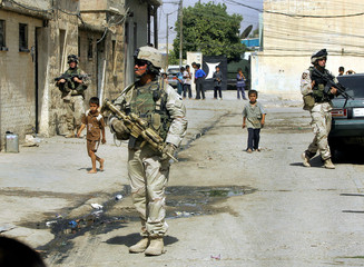 US soldiers walk through streets during patrol in Mosul.
