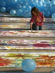 A child paints a flower on the world's longest painting ever made by children in Bucharest