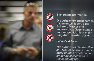 A passenger stands beside a sign with the security advice inside the main terminal of airport