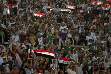 Iraqi fans cheer during a West Asian Football Federation Championship soccer match between Iraq and Iran in Amman