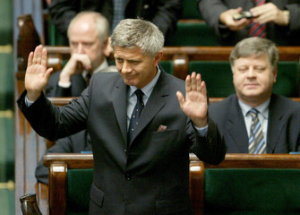 POLISH PRIME MINISTER MAREK BELKA RAISES HIS ARMS SURROUNDED WITH MEMBERS OF HIS CABINET JUST AFTER ...