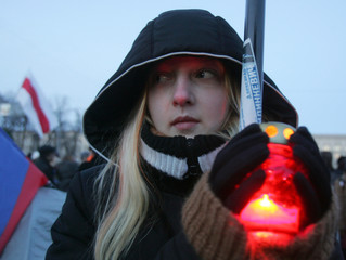 Supporter of opposition presidential candidate Milinkevich warms hands over candle in Minsk