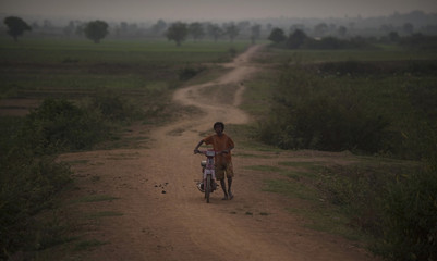 A man pushes his bike down a dirt road near Udong