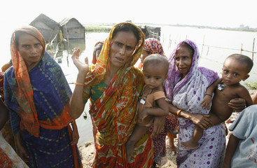 Women stand on a road after leaving their flooded homes in Basila