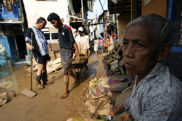 Elderly woman sits in front of her house while residents clean up mud in east Jakarta