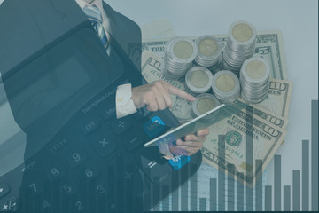Double exposure businessman using tablet manage his business on stack of coins and calculator.