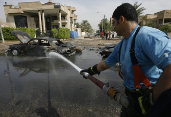 A fireman hoses down a burnt vehicle after a car bomb attack in Baghdad