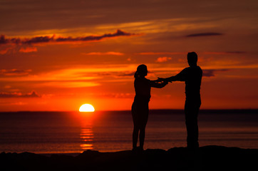 Silhouettes of woman and man on a background of colorful sunset of a cloudy day on the beach