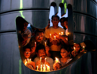 Activists from Anti Terrorist Front hold lighted candles in Chandigarh