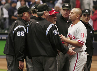 Philadelphia Phillies Shane Victorino tries to break up a double play by running into Milwaukee Brewers Craig Counsell in the the ninth inning during Game 3 of their MLB National League Divisional Series playoff baseball game in Milwaukee